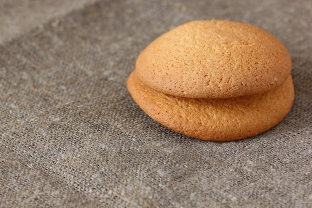 Biscotti di farina d'avena due pezzi sulla tovaglia di tela ruvida.