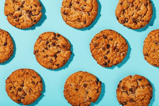 Biscotti di farina d'avena con motivo a gocce di cioccolato e motivi su sfondo azzurro.