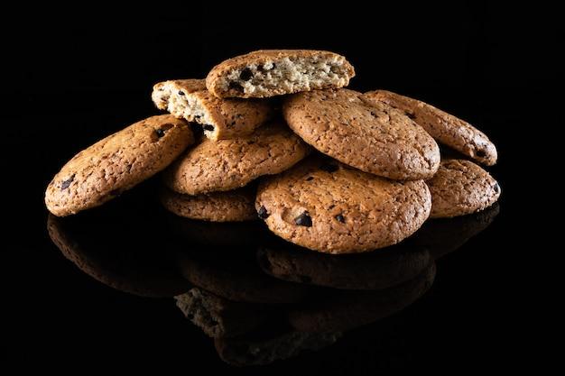 I biscotti di farina d'avena con gocce di cioccolato sono isolati su uno sfondo nero con un riflesso. un sacco di biscotti fatti in casa rotondi marroni che si trovano su una superficie riflettente, primo piano.