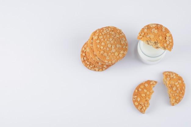 Biscotti di farina d'avena con semi di sesamo e un bicchiere di latte su un tavolo bianco.