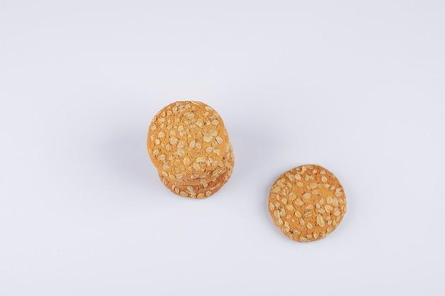 Biscotti di farina d'avena con semi di sesamo su un tavolo bianco.