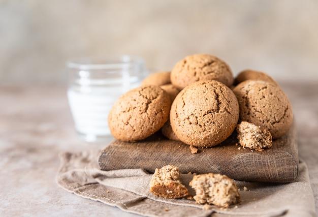 Biscotti di farina d'avena su tagliere di legno con una tazza di latte spuntino sano o dessert