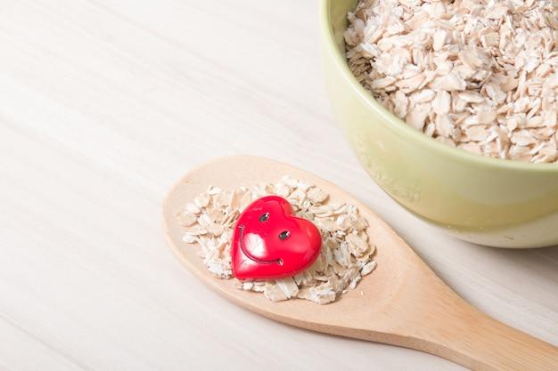 Farina d'avena in una ciotola verde e un cucchiaio di legno grande con farina d'avena e un piccolo cuore rosso felice su un tavolo di legno