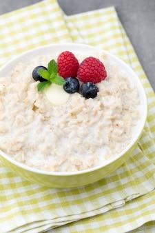 Porridge di farina d'avena in una ciotola con lamponi e more.