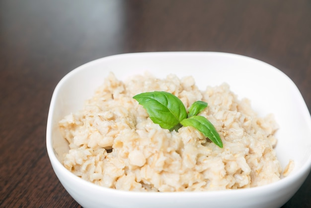 Porridge di farina d'avena, porridge d'avena, cereali per la colazione decorati con foglie verdi sulla tavola di legno.