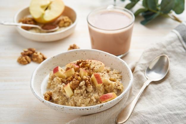 Porridge di farina d'avena con mela, noci e tazza di cacao su luce di legno bianca