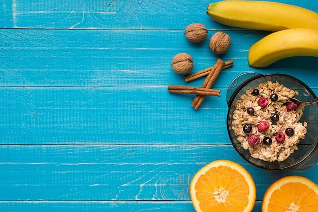 Porridge di farina d'avena con banana, kiwi, noci e miele in una ciotola con uova per una sana colazione su r...