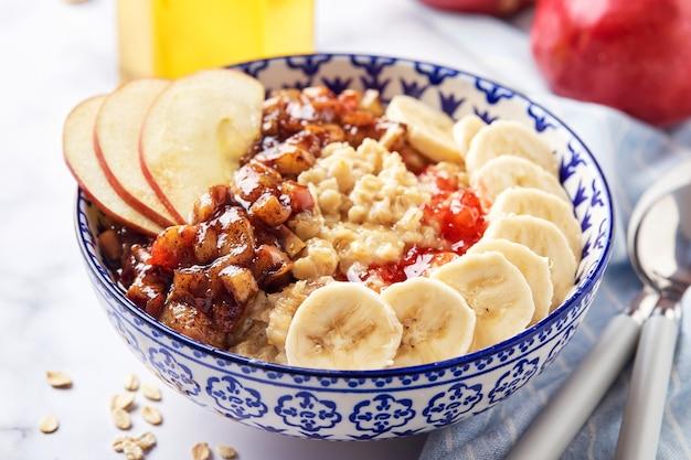 Porridge di farina d'avena con mele caramellate con cannella, banana, fragole grattugiate e miele su sfondo di marmo chiaro, primi piani