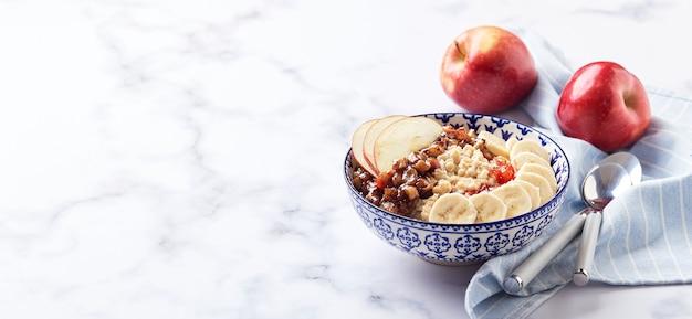 Porridge di farina d'avena con mele caramellate con cannella, banana, fragole grattugiate su fondo di marmo chiaro. banner lungo e largo con posto per il testo.