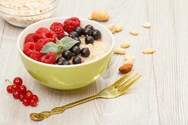 Porridge di farina d'avena con bacche di ribes e lamponi, forchetta, ciotole di vetro con fiocchi d'avena