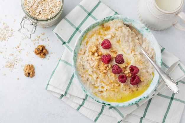 Porridge di farina d'avena con lamponi freschi, noci e burro in un piatto di ceramica su una pietra chiara o cemento.