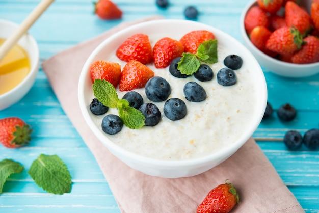 Porridge di farina d'avena con latte, bacche fresche e miele in uno spazio rustico