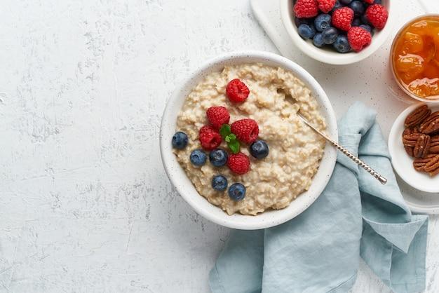 Porridge rustico di farina d'avena con mirtilli, lamponi, marmellata e noci in una ciotola bianca, un trattino dieta