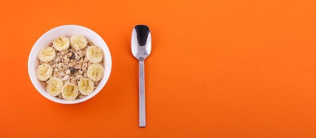 Farina d'avena in piatto bianco con banana a fette e cucchiaio su sfondo arancione cibo sano concept