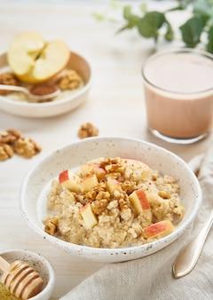 Farina d'avena con mela, noci, cannella, miele e tazza di cacao su luce bianca in legno