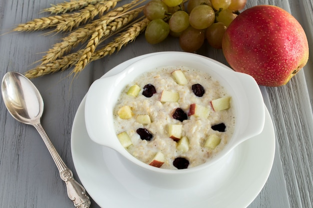 Farina d'avena con mela e uvetta nel piatto bianco