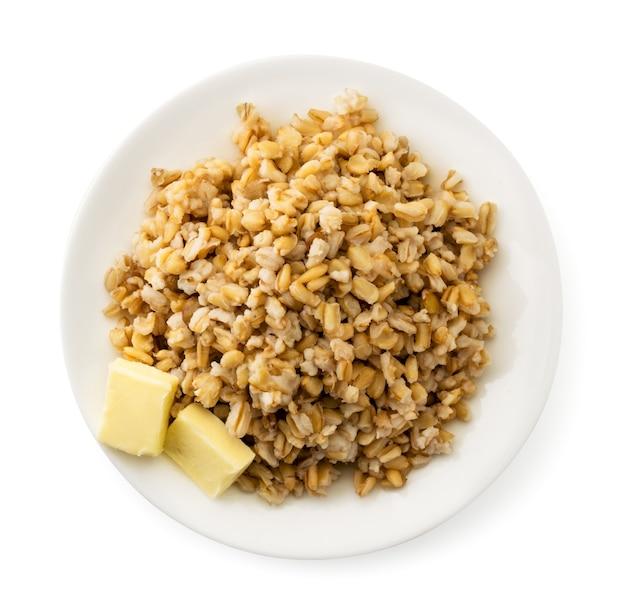 Farina d'avena con burro in un piatto su bianco