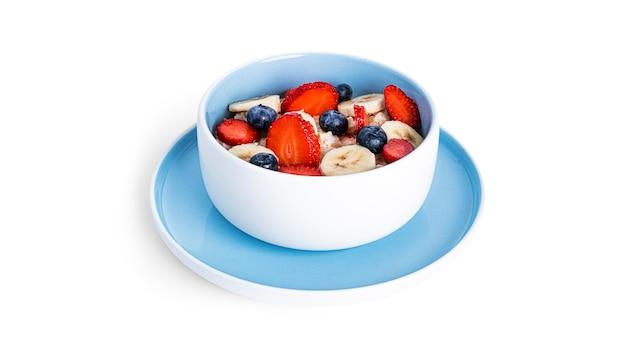 Farina d'avena con frutta isolata on white. farina d'avena con fragole, mirtilli e banana.