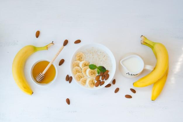Farina d'avena con miele, banana e noci in un piatto su un muro bianco con il resto degli ingredienti si trovano al centro del telaio. vista dall'alto.