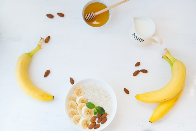 Farina d'avena con miele, banana e noci in un piatto su un muro bianco con il resto degli ingredienti. vista dall'alto. disteso.