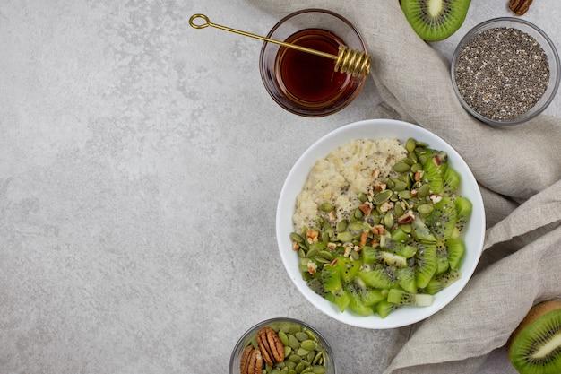 Farina d'avena con kiwi, noci pecan, semi di zucca, semi di chia, sciroppo d'acero o miele in una ciotola per la colazione su sfondo di cemento chiaro.