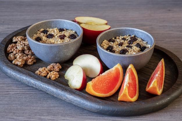 Farina d'avena con uvetta, mele, arance, noci su un vassoio di quercia. mangiare sano. una dieta ricca di fibre. uno stile di vita sano.