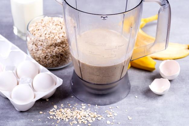 Avena e uova in un frullatore. frittelle di avena con banana. processo di cottura graduale. banane, latte, uova, avena, sale.