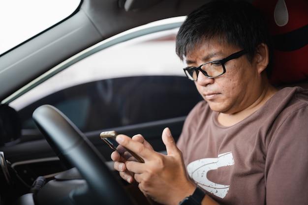 Uomo asiatico obeso con occhiali senza cintura di sicurezza che guarda lo smartphone per controllare il messaggio di testo durante l'ingorgo stradale, la guida pericolosa, distrarsi dall'attenzione può causare un incidente d'auto