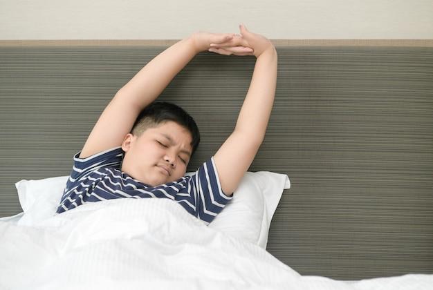 Il ragazzo grasso obeso si sveglia e si allunga sul letto la mattina, l'assistenza sanitaria e il concetto di mondo del buongiorno