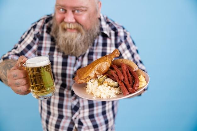 Uomo obeso su sfondo blu concentrarsi sulle mani con piatto di cibo grasso e birra
