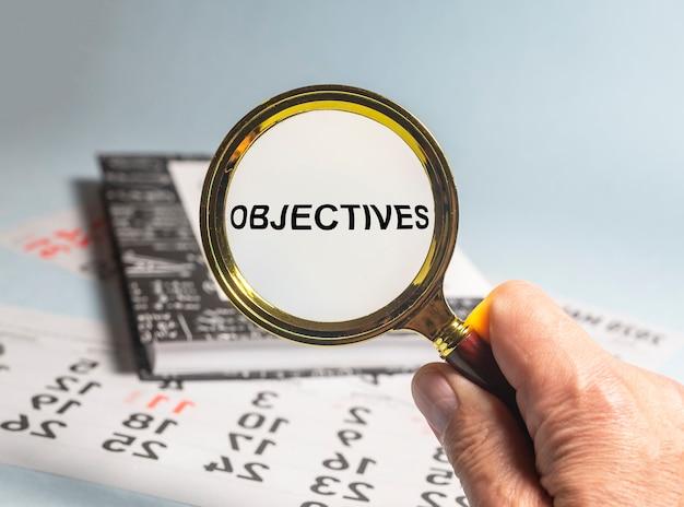 Obiettivi parola iscrizione attraverso la lente di ingrandimento su documenti finanziari, obiettivi aziendali.
