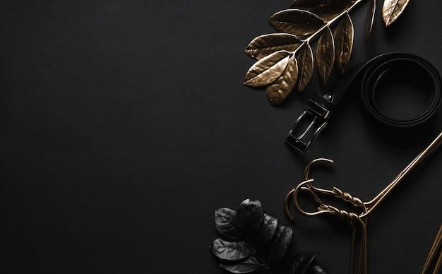 Oggetti di lusso sul tavolo nero. accessori uomo e attrezzature di bellezza e piante di lusso minimali. vista dall'alto con spazio di copia.