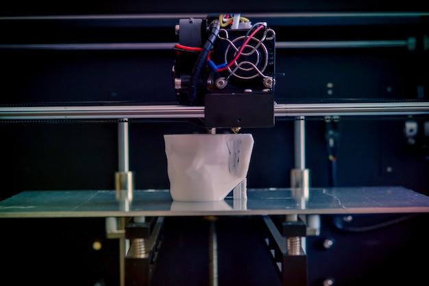 Oggetti stampati da stampante 3d. filtro scuro. copia spazio. la stampante 3d tridimensionale automatica esegue la modellazione plastica in laboratorio. tecnologia additiva moderna e progressiva