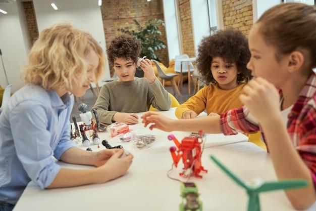 Gruppo di osservazione di ragazzini vivaci che discutono di giocattoli tecnici ed esaminano i dettagli mentre