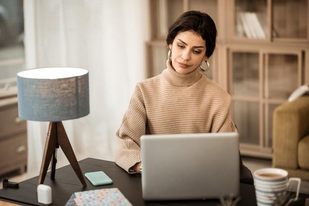 Osservare le informazioni. sorridente donna allegra con i capelli lunghi seduto alla scrivania e godersi il suo lavoro
