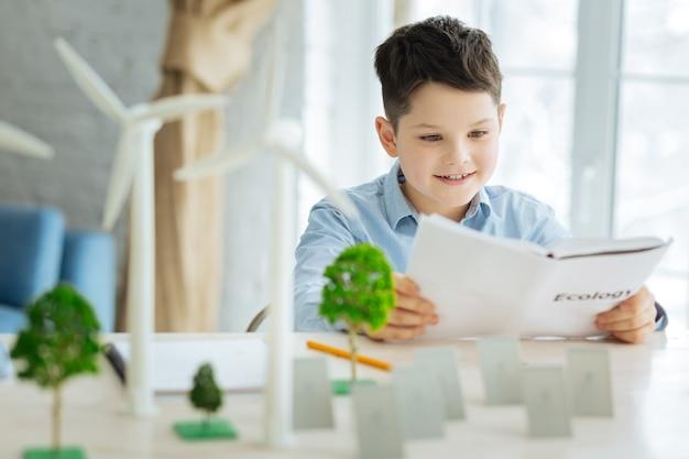 Ottenere la conoscenza. adorabile ragazzo pre-adolescente che impara a conoscere l'ecologia e le energie alternative in particolare durante la lettura del libro, seduto al tavolo pieno di modelli di alberi, pannelli solari