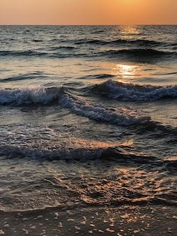 Oceano, onde del mare al tramonto, alba con riflessi del sole sull'acqua