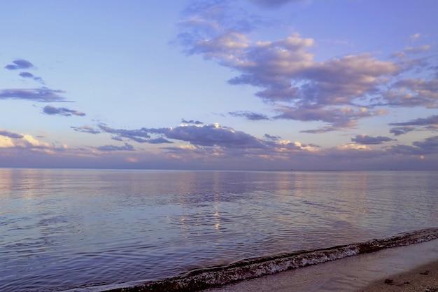 Onde dell'oceano e costa. barca a vela sullo sfondo. bellissimo cielo al tramonto.