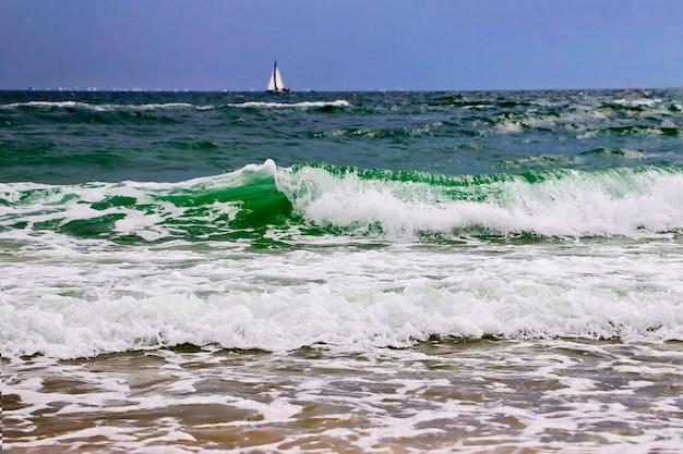 Onde dell'oceano e costabarca a vela sullo sfondospuma d'acqua nella sabbia