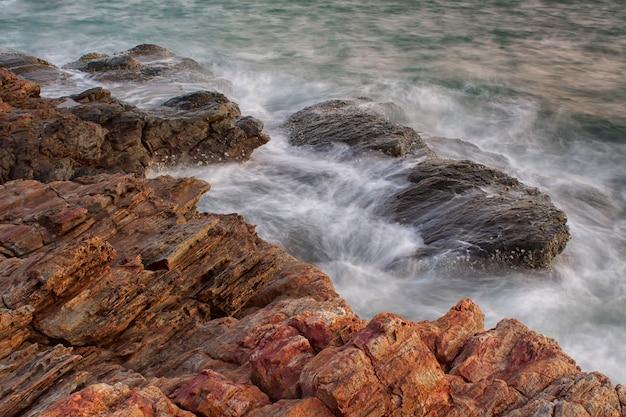 Onde dell'oceano che si infrangono sulle rocce
