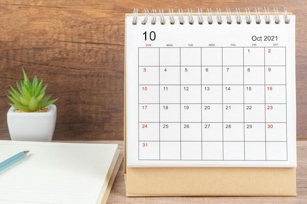Mese di ottobre, scrivania del calendario 2021 per l'organizzatore per la pianificazione e il promemoria sul tavolo. concetto di riunione di appuntamento di pianificazione aziendale