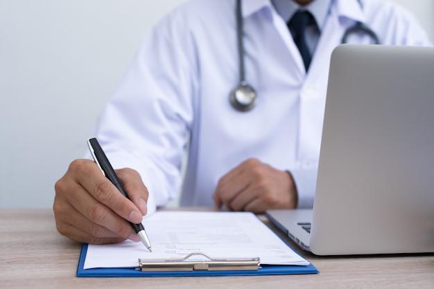 Octor compilando un documento medico che lavora presso l'ufficio dei medici