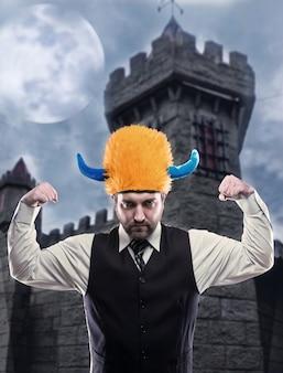 Strano uomo d'affari nel casco del partito che mostra la sua forza contro l'antica torre