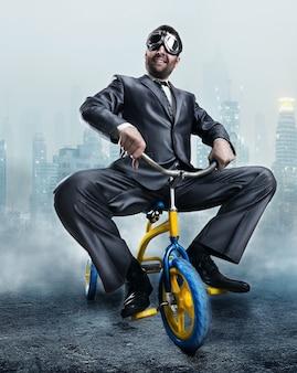 Strano uomo d'affari in sella a una piccola bicicletta contro la città oscura