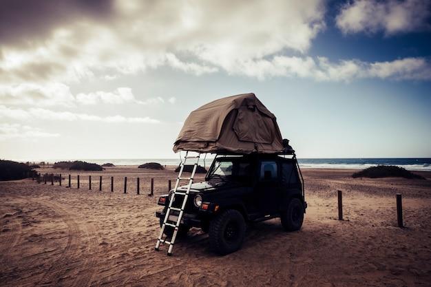 Vita fuori dal concetto di indipendenza dalla griglia con un'auto fuoristrada nera e una tenda sul tetto per dormire e vivere da soli nella natura selvaggia