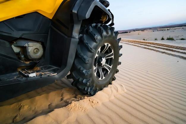 Fuoristrada atv car closeup dettaglio grande pneumatico, irriconoscibile. primo piano della ruota dell'atv. il turista in quad attraversa il deserto sabbioso.