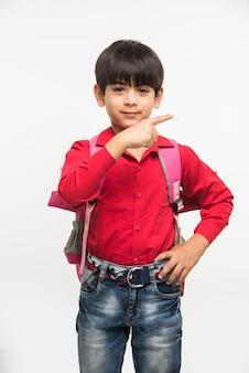 Via a scuola - simpatico ragazzino indiano o asiatico in camicia rossa e jeans denim con borsa da scuola, in piedi isolato su sfondo bianco