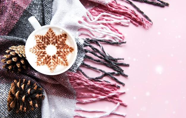 Ð¡offee con un motivo a fiocco di neve su una calda superficie in plaid di lana