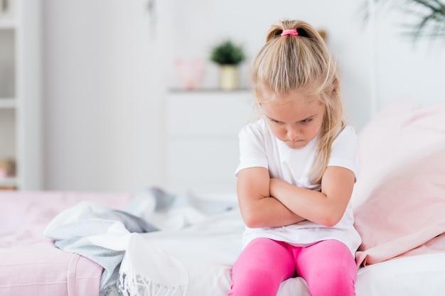 Bambino offeso o annoiato in abbigliamento casual che incrocia le braccia sul petto mentre è seduto sul divano di casa
