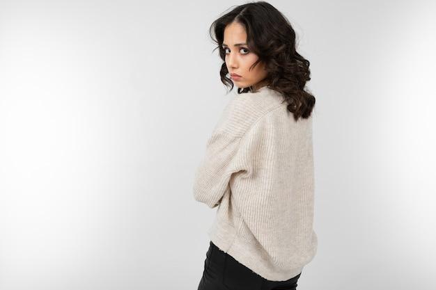Ragazza offesa in maglione bianco lavorato a maglia in piedi su isolato con spazio di copia